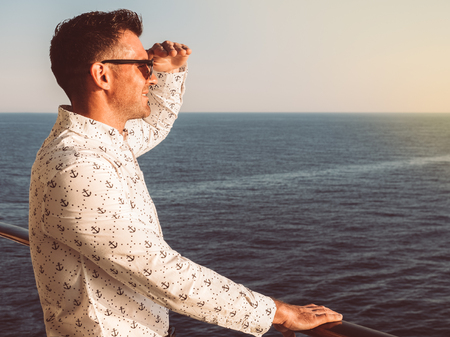Attractive man in a white shirt with patterns in the form of anchors