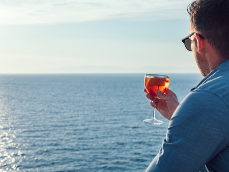 Attractive, stylish man in sunglasses, holding a glass of beautiful pink cocktail