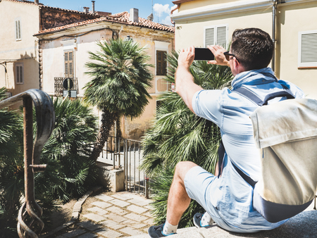 Stylish, attractive traveler with smartphone photographing old building