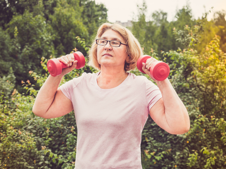 Cute, adult woman doing exercises with pink dumbbells