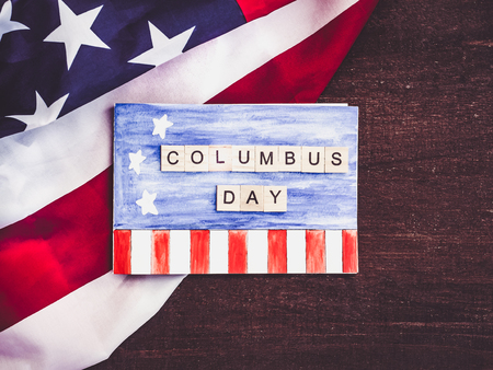 Blank notepad page with a pattern, wooden letters of the alphabet in the form of words Columbus day against the background of the US flag and wooden surface. Close-up. Preparing for the celebration