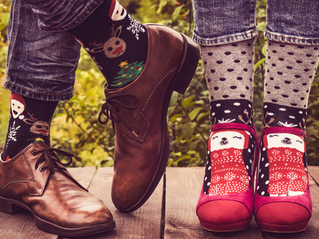 Female and male legs in stylish shoes, bright, colorful socks with a Christmas and New Year pattern on the background of trees. Lifestyle, fashion, fun