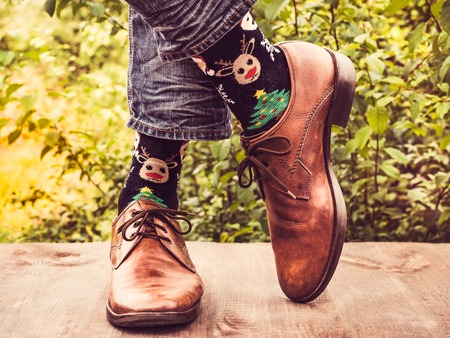 Office manager in stylish shoes, jeans and bright, colorful socks with a Christmas and New Year pattern on the background of trees. Lifestyle, fashion, fun Stock Photo