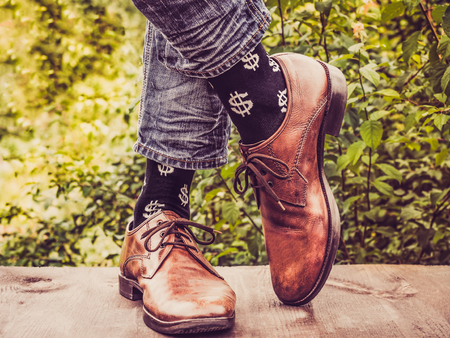 Office manager in stylish shoes, jeans and socks with patterns in the form of US dollars against the background of green trees. Lifestyle, fashion, fun