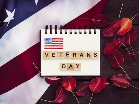 Notepad with blank page, wooden letters of the alphabet in the form of words Veterans day against the background of the US flag, purple leaves and wooden surface. Preparing for the celebration