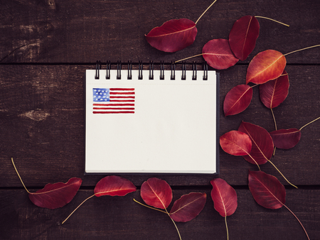 Blank invitation card for Your inscriptions on a background of the US Flag and an vintage wooden surface. Top view, close-up. Preparing for the holidays Stock Photo
