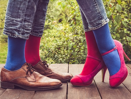 Legs of a young couple in stylish shoes, bright, colorful socks on a wooden terrace against the background of green trees. Lifestyle, fashion, fun