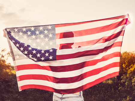 Attractive man holding a US flag against the background of the rays of the setting sun. View from the back. Preparing for the holidays Stock Photo