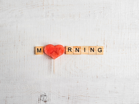 Wooden letters in the form of the word MORNING, a slice of watermelon and a shabby surface of white color. Top view, close-up, isolated. Preparation for the holiday. Congratulations for loved ones