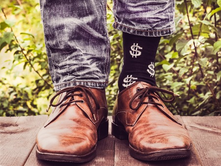 Mens legs in stylish shoes, black socks with patterns in the form of US dollars on a wooden terrace against the background of green trees. Beauty, fashion, elegance