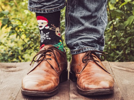 Mens legs in stylish shoes, bright, variegated socks with Christmas and New Years patterns on the wooden terrace on the background of green trees. Beauty, fashion, elegance