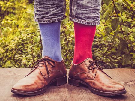Gambe degli uomini in scarpe eleganti, calzini luminosi, multicolori, variegati con motivi natalizi e di Capodanno sulla terrazza in legno sullo sfondo di alberi verdi. Bellezza, moda, eleganza