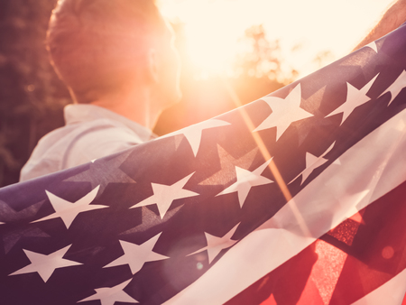 Attractive man holding waving in the wind US flag against the backdrop of the rays of the setting sun. View from the back, closeup. Preparing for the holidays