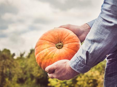 Young man in a denim shirt holding a ripe pumpkin
