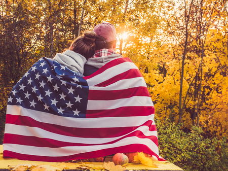 Happy married couple holding the US flag
