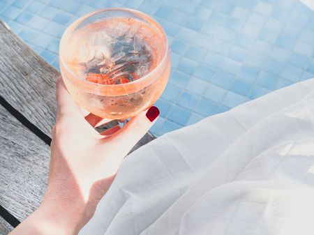 Beautiful glass with a pink cocktail and ice cubes on the background of the pool with blue water. Top view, close-up. Rest during a sea cruise