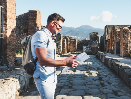 Handsome man in sunglasses looking at a map with landmarks against the backdrop of historic ruins, blue sky and the rays of the setting sun. Italy, Pompeii. Travel and vacation concept Imagens