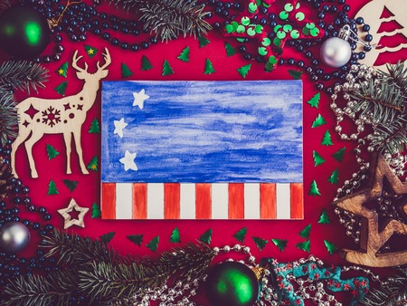 Colorful decorations, multicolored confetti, Christmas tree branches, blank notebook page with a USA flag drawing on a red surface. Top view, close-up, flat lay. Merry Christmas and a Happy New Year Stock Photo