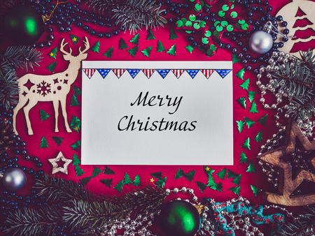 Colorful Christmas decoration, silver beads, Christmas tree branches, drawing and inscription in notebook on a red surface. Top view, close-up, flat lay. Greeting card