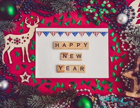 Colorful New Year decorations, silver beads, branches of the Christmas tree, drawing in a notebook on a red surface. Top view, close-up, flat lay. Greeting card Stock Photo