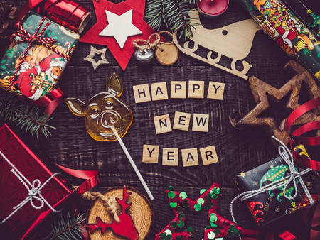 Box with gifts, colorful decorations, Christmas tree branches, candles and cones on a wooden, brown surface. Top view, close-up, flat lay. Greeting card. Merry Christmas and Happy New Year