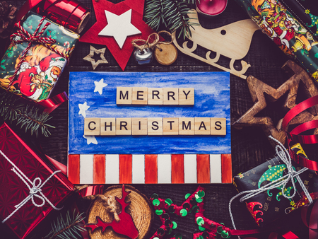 Greeting card with US Flag drawing, New Year and Christmas decorations, boxes with gifts on a brown surface. Top view, close-up, flat lay. Merry Christmas and Happy New Year Stock Photo