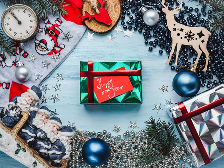 Box with gifts, colorful decorations, multicolored confetti, Christmas tree branches on a wooden, blue surface. Top view, close-up, flat lay. Merry Christmas and Happy New Year Stock Photo