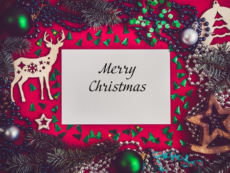 Merry Christmas and a Happy New Year. Colorful decorations, multicolored confetti, Christmas tree branches on a red surface. Top view, close-up, flat lay