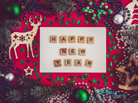 Colorful decorations, silver beads, Christmas tree branches, drawing and inscription in notebook on a red surface. Top view, close-up, flat lay. Happy New Year