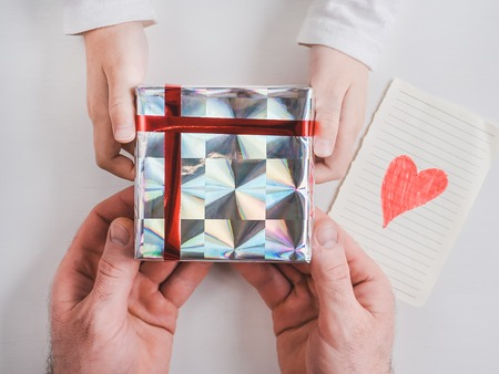 Bright box with a gift, tied with a ribbon, hands of a loving father and hands of a child on a white, isolated background. Top view, close-up. Preparing for the holidays. Happy family concept Stock Photo