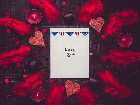 Sheet of paper with the handwritten inscription LOVE YOU on the background of candles, hearts and pink feathers. Dark background. Flat lay, close-up. Festive invitation and greeting card design Archivio Fotografico