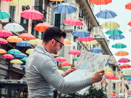 Handsome man with a tourist map on the background of a beautiful street of the fabulous city of Genoa on a cloudy, rainy day. Travel and vacation concept Standard-Bild
