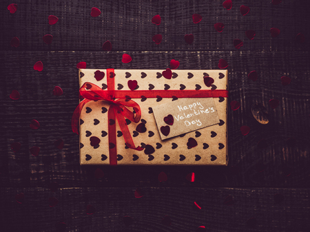Colorful gift box on a dark surface background. Flat lay, close-up. Congratulations to loved ones, relatives, friends and colleagues on Valentines Day