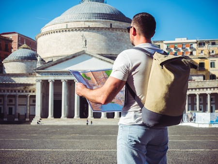 Handsome man holding a map against the background of the empty square in the beautiful city of Naples, Italy Stock Photo