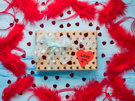 Box with a gift, tied with a ribbon, note with sweet words of love and tinsel in the shape of hearts. Close-up, flat lay, isolated. Congratulations for loved ones, relatives, friends and colleagues