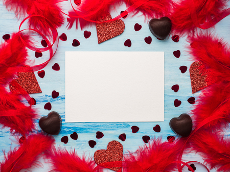 Blank space for sweet words of love. Ribbons, colorful feathers, candy and heart-shaped tinsel. Top view, isolated. Congratulations to family, friends and colleagues