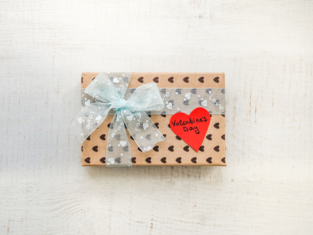 Box with a gift, tied with a ribbon, a note with sweet words of Love and tinsel in the shape of hearts. Top view, close-up, flat lay, isolated background. Preparing for Valentines Day