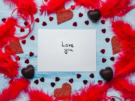 Note with sweet words of love, ribbons, colorful feathers, candy and tinsel in the shape of a heart. Top view, isolated background. Congratulations for loved ones, relatives, friends and colleagues