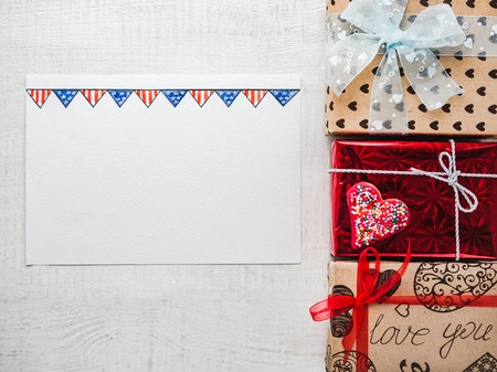 Blank Notepad Page for sweet words about love, bright gift boxes and confetti on a wooden white surface of the boards. Closeup, flat lay. Congratulations for loved ones, relatives, friends, colleagues Stockfoto