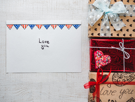 Blank Notepad Page for sweet words about love and bright gift boxes on a wooden white boards. Closeup, flat lay. Congratulations for loved ones, relatives, friends, colleagues Stock Photo