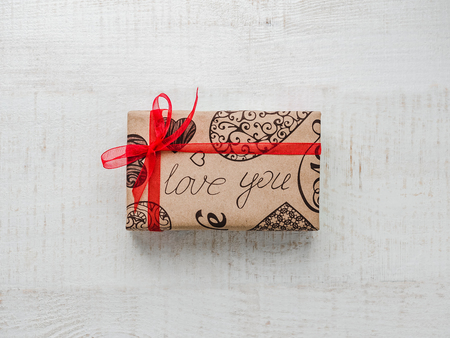 Postcard for sweet words of love and bright gift boxes on a white, wooden table. Closeup, flat lay. Congratulations to friends, family, friends, colleagues