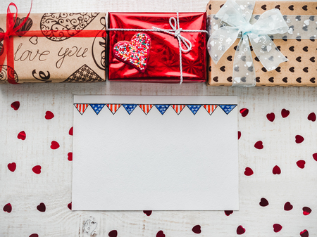 Blank Notepad Page for sweet words about love, bright gift boxes and confetti on a wooden white surface of the boards. Closeup, flat lay. Congratulations for loved ones, relatives, friends, colleagues Stock Photo