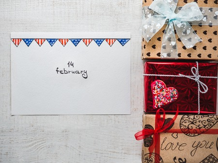 Happy Valentines Day. Bright gift boxes tied with a ribbon, a note with sweet words about love and confetti. Closeup, flat lay. Congratulations for loved ones, relatives, friends and colleagues
