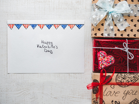 Happy Valentine's Day. Bright gift boxes tied with a ribbon, a note with sweet words about love and confetti. Closeup, flat lay. Congratulations for loved ones, relatives, friends and colleagues