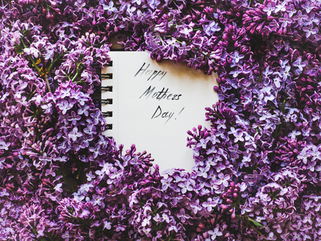 Happy Mothers Day! Notepad, page with the inscription, bright lilac flowers. Top view, close-up. Preparation for the holiday