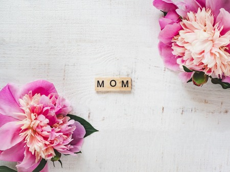 Colorful peonies and wooden letters of the alphabet in the form of the word MOM on a white isolated background. Top view, close-up. Beautiful card. Congratulations for your beloved mother