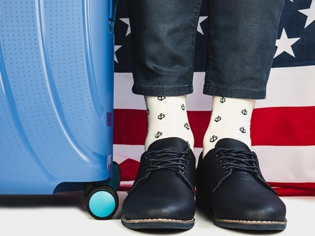 Stylish, beautiful suitcase, US Flag, men's legs, bright socks with a nautical theme and shoes on a white, isolated background. Close-up. Concept of style, fashion, beauty and travel