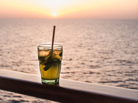 Beautiful glass, bright cocktail with ice and straw, standing on the open deck against the backdrop of sea waves and sunset. Side view, close-up. Concept of leisure and travel