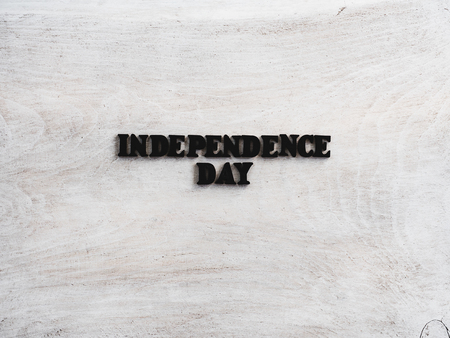 Beautiful greeting card for Independence Day. Wooden letters with a congratulatory inscription on a white background. Close-up, top view. Congratulations for loved ones, relatives, friends, colleagues