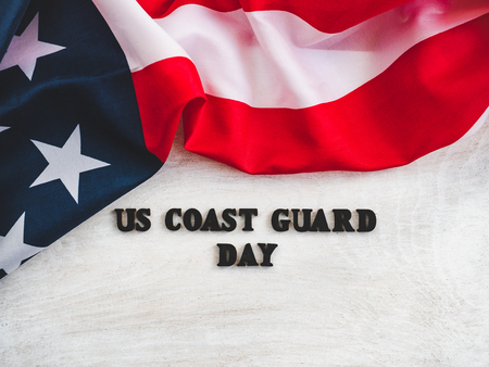 Beautiful card for US Coast Guard Day. Wooden letters with a congratulatory inscription on a white background. Close-up, top view. Congratulations for loved ones, relatives, friends and colleagues